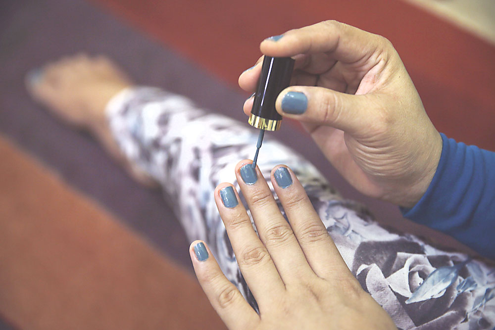 A transgender person applies nail polish to her fingernails at her office in Banda Aceh, Indonesia, on Thursday.   REUTERS