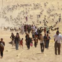 Displaced people from the minority Yazidi sect flee toward the Syrian border on Aug. 10 following an onslaught by Islamic State forces on the town of Sinjar, on the outskirts of Iraq's Sinjar mountain. | REUTERS