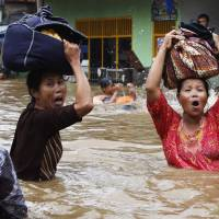 Women flee a flooded area in Jakarta in January 2013. Floods and severe storms have become more common in Southeast Asia in recent decades. | REUTERS