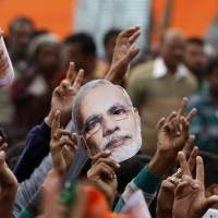 Supporters of India's ruling Bharatiya Janata Party hold up masks of Prime Minister Narendra Modi during an election campaign rally in Kathua, about 90 km from Jammu, in India on Saturday. | AP