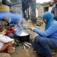 A Syrian refugee with her children prepares food near her tent last December as a heavy snowstorm batters the region, including the camp for Syrians who fled their country's civil war in the Chouf mountain town of Ketermaya, Lebanon. The U.N. World Food Program says it has suspended a food voucher program serving more than 1.7 million Syrian refugees because of a funding crisis. The WFP says the program provided Syrian refugees in Jordan, Lebanon, Turkey, Iraq and Egypt with vouchers to buy food in local shops. | AP