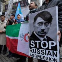 Crimean Tatars stage a protest against Russian President Vladimir Putin's visit to Istanbul on Monday. | AP