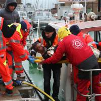 A rescued sailor is brought ashore in the harbor at Ravenna on Sunday. Three seamen were missing, feared drowned after a Turkish-registered merchant ship sank off Italy following a collision with a Belize-registered vessel in rough Adriatic seas, the coast guard said. | AFP-JIJI