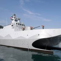 Taiwan Navy sailors and officers wave as the Taiwan-made patrol guard corvette Tuo Jiang sets sail during the handover ceremony at Suao port in Yilan county, northeast Taiwan, on Tuesday.   AP