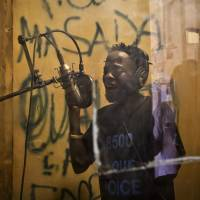 Hood Katende, a 26-year-old reformed thief and onetime drug peddler who now produces music encouraging AIDS awareness, performs on Nov. 5 in a small shipping container-turned-recording studio in the Kamwokya slum of Kampala. As World AIDS Day is marked on Monday, Uganda and many other African countries are continuing their battle against HIV and AIDS, and Ugandan street activists like Katende are trying to use music and drama to stem a troubling resurgence of HIV, which now infects more than 500 young women between the ages of 15 and 24 each week, according to the Uganda AIDS Commission. | AP