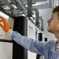 A researcher operates a computer analyzing genomes in this undated file photo. | COURTESY OF GENOME RESEARCH LTD./KYODO