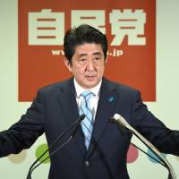 Prime Minister Shinzo Abe holds a news conference on Monday at Liberal Democratic Party headquarters in Tokyo following his election triumph. | AFP