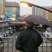People listen in the rain to a campaign speech in the city of Tama in western Tokyo last Thursday.   KYODO