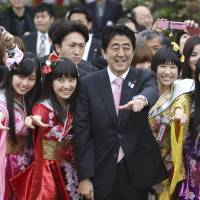 Prime Minister Shinzo Abe strikes a pose with the Momoiro Clover Z pop group during his cherry blossoms viewing garden party in April 2013 at Shinjuku Gyoen National Garden in Tokyo. | AP