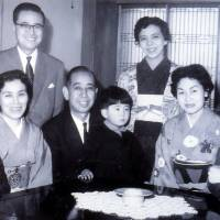 Young Shinzo Abe (center) sits on the lap of his grandfather, Prime Minister Nobusuke Kishi, in an undated family photo. | SHINZO ABE'S OFFICE/AP