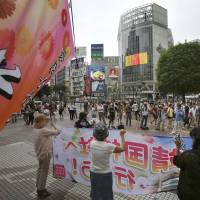 Activists from the Hanadokei women's group hold a banner reading 'Go to Yasukuni Shrine!' as they solicit support from passers-by in Tokyo's Shibuya shopping district on Aug. 14.   AP