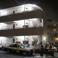Investigators assemble Sunday night in front of an apartment in Atsugi, Kanagawa Prefecture, where an unidentified body was found wrapped in taped-together plastic bags. The residents of the unit were reported missing.