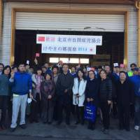 Residents and staff of Keyaki no Sato in Kawagoe, Saitama Prefecture, join visitors from the Beijing Association of Rehabilitation for Children with Autism for a commemorative photo on Dec. 5.   KEYAKI NO SATO