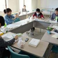 Members of a student worker union in Sapporo discuss labor laws at a meeting on the campus of Hokkaido University in March. | KYODO
