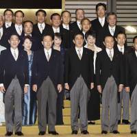 Prime Minister Shinzo Abe and members of his Cabinet take part in a photo session on Wednesday evening at the Imperial Palace following their attestation ceremony. | KYODO
