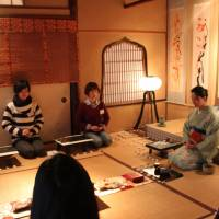 Digital detox participants in Atami, Shizuoka Prefecture, meditate with stones Dec. 6 as they try to resist the lure of Facebook. | KYODO
