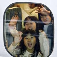 A mother and her daughters wave as they leave JR Shin-Osaka Station aboard a bullet train Saturday, the first day of the yearend holidays. | KYODO
