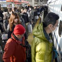 People board a bullet train at Shin-Osaka Station on Tuesday, leaving for their hometowns for the New Year's holidays.   KYODO