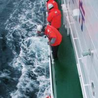 A crew member of the Cambodia-registered freighter Ming Guang is rescued from the Sea of Japan off Aomori Prefecture on Friday. | 2ND REGIONAL JAPAN COAST GUARD HEADQUARTERS/KYODO
