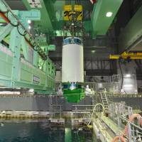 Some of the last nuclear fuel rod assemblies to be removed from the teetering fuel pool above the No. 4 reactor are winched out of the heavily damaged building to a more secure facility in a transport container (center) Saturday at the Fukushima No. 1 plant. | POOL/KYODO
