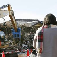 A former Futaba resident, now living as an evacuee in Iwaki, Fukushima Prefecture, watches on Wednesday as tsunami debris is removed for the first time since the nuclear disaster. | KYODO