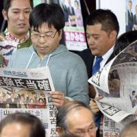 Supporters read a newspaper's Sunday night extra edition reporting the victory of Seiken Akamine, of the Japanese Communist Party, in the Okinawa No. 1 constituency. | KYODO