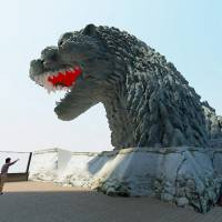 In an illustration provided by Toho Co., Godzilla smashes through the eighth-floor terrace of a Toho building in Tokyo's Shinjuku district. When completed, the sculpture will stand 12 meters tall. | TOHO CO./KYODO