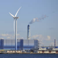 A wind turbine is shown in front of a thermal power station in Yokohama. | ISTOCK