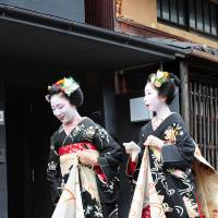 Two 'maiko,' or apprentice geisha, pay a round of visits to their teachers of traditional Japanese arts and teahouse owners during the annual summer 'hassaku' event in Kyoto's Gion district on Aug.1. | COURTESY OF DONALD KEENE