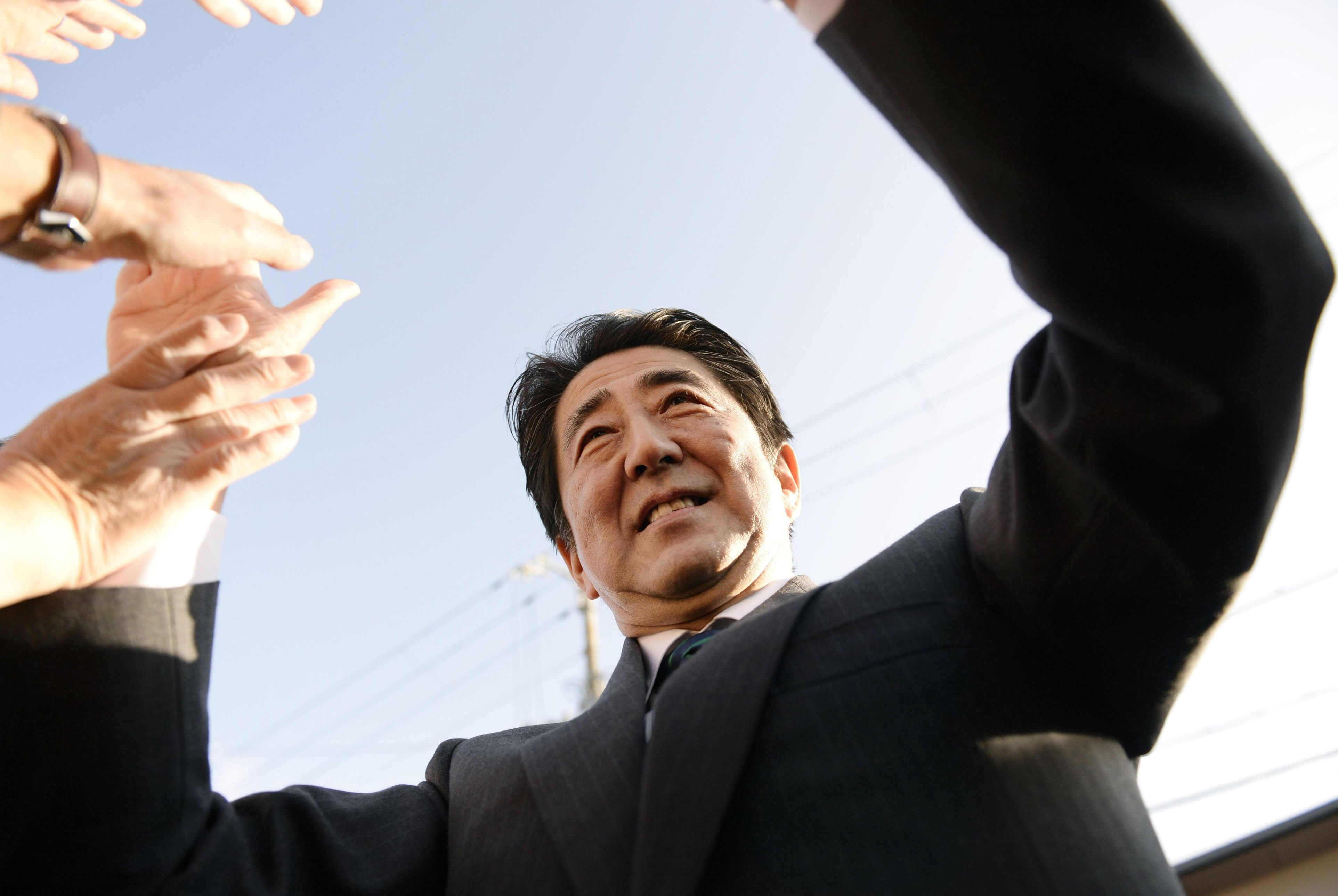 Prime Minister Shinzo Abe high-fives supporters in Kyoto on Dec. 10 while campaigning for the Lower House election. | KYODO