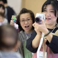 Yuka Suzuki (right) gives a class of young parents tips on how to photograph baby portraits, in Tokyo on Oct. 18. As Prime Minister Shinzo Abe heads into the election promising to unlock the economic potential of women, the problem of single mothers living in poverty underscores the gender divide. | BLOOMBERG
