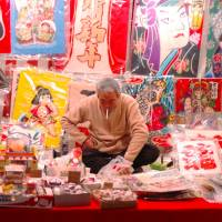 A worker is surrounded by many decorative kites. | ANOTHER SIDE OF YUKITA FROM ASAKUSA/WIKIMEDIA