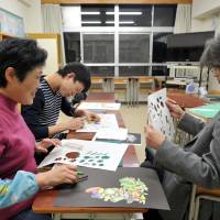 Dong Xiao Mong (left), a student from China, takes an art lesson at Bunka Junior High School in Tokyo on Dec. 10. | YOSHIAKI MIURA