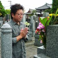 Akira Kawai of Ota Ward, Tokyo, prays in front of the grave of his daughter, Shiori, who died in 2009 at age 11 after being admitted to Tokyo Women's Medical University Hospital and undergoing heart surgery. | KYODO
