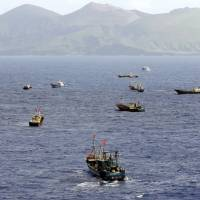 Boats operated by Chinese coral poachers dot the ocean near the Ogasawara Islands, south of Tokyo, on Oct. 31. | KYODO