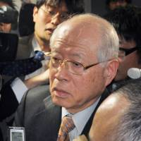 Riken President Ryoji Noyori is surrounded by reporters at the science ministry in Tokyo on Friday afternoon after the institute announced it has given up all efforts to verify the existence of pluripotent stem cells produced by a new method that Riken researcher Haruko Obokata claimed to have discovered. | KYODO