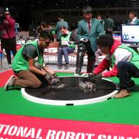 A member of the Mexican team Ezimes Robots (left) and his opponent from the Colombian team Bucaros prepare for a bout in the autonomous robot division during the International Robot Sumo Tournament at Ryogoku Kokugikan in Tokyo on Sunday.  | KAZUAKI NAGATA