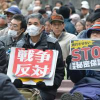 Protesters hold signs reading, from right, 'Stop secrets protection law' and 'Oppose war' during a rally in Tokyo on Saturday. The law took effect on Wednesday. | AFP-JIJI