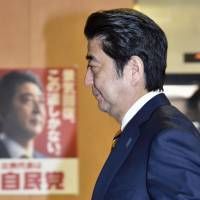 Prime Minister Shinzo Abe enters the Liberal Democratic Party headquarters in Tokyo shortly before polls closed Sunday evening for the House of Representatives snap election. | KYODO