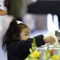 A girl casts an adult's ballot in Tokyo on Sunday. | REUTERS