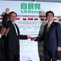 Prime Minister Shinzo Abe (second from right) shakes hands with Liberal Democratic Party Secretary-General Sadakazu Tanigaki as party Vice President Masahiko Komura (left) and election chief Toshimitsu Motegi applaud at party headquarters in Tokyo on Sunday night. | YOSHIAKI MIURA