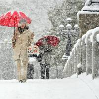 People walk in heavy snow in the city of Hiroshima on Wednesday morning. | KYODO