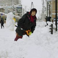 A woman shovels snow Sunday on a shopping street in the city of Aomori. Some areas got a meter or more of snowfall. | KYODO