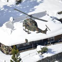 A Ground Self-Defense Force helicopter lowers a crewman to check on snowbound residents in Tsurugi, Tokushima Prefecture, on Monday. | KYODO
