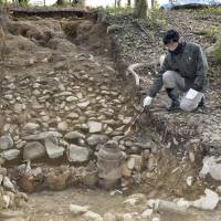 A man points to pots excavated at Tannowa Nisanzai Kofun, an ancient burial mound in the town of Misaki, Osaka Prefecture, on Friday. | KYODO