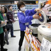 A sales clerk helps Chinese tourists at a Laox electronics store in Tokyo's Akihabara district in January 2012. | BLOOMBERG