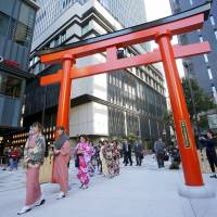 Foreigners wearing kimono walk through a torii in Tokyo's Nihonbashi district in November. The travel industry is hoping tourists will venture away from the nation's biggest cities. | AP