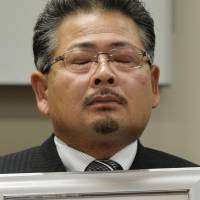Yasushi Saijo holds a photo of his late daughter at a news conference in Sendai on Wednesday. | KYODO