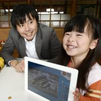 A girl shows a picture drawn with a Plainnovation Inc. app to founder Motoshi Kanke at a nursery school in Fukushima Prefecture on Oct. 17. | KYODO