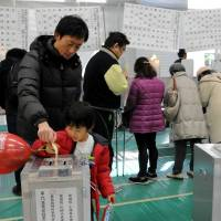 Voters cast ballots for the Lower House election at a polling station in Minato Ward, Tokyo, on Sunday.   SATOKO KAWASAKI